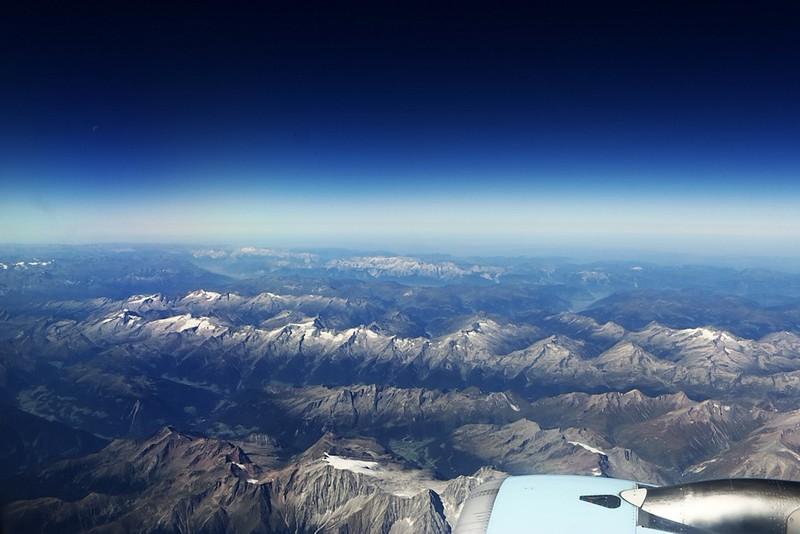 Hranice Rakouska a Itálie. Za přední částí motoru vykukuje vrcholek Hochgall z pohoří Rieserferner, který leží přímo na hranici, za ním v údolí městečko Riva di Tures. Středem fotografie se táhne hřeben Zillertalských Alp.