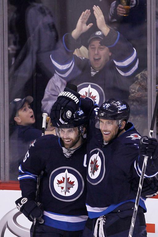 . Winnipeg Jets\' Andrew Ladd (16) and Blake Wheeler (26) celebrate Wheeler\'s goal against Colorado Avalanche\'s goaltender Semyon Varlamov (1) during first period NHL hockey action in Winnipeg, Manitoba,  on Thursday, Dec. 12, 2013. (AP Photo/The Canadian Press, John Woods)