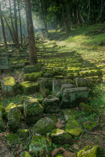 Sunbeam lighting on the moss covered rocks near pond at Angkor Wat