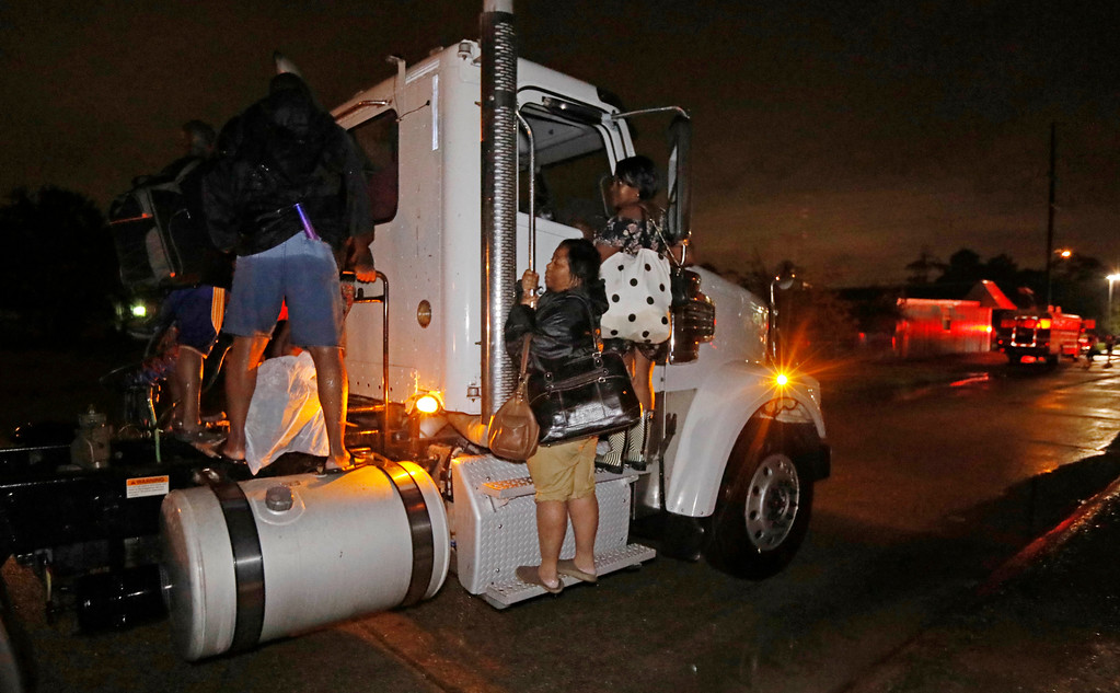 . Residents cling to a commercial truck as it carries them to safety following flooding to their homes, late Monday night, Aug. 28, 2017, in Lake Charles, La. Almost constant rain over the last two days from Harvey, overcame the city\'s drainage system, flooding several subdivisions and necessitating home rescues. (AP Photo/Rogelio V. Solis)
