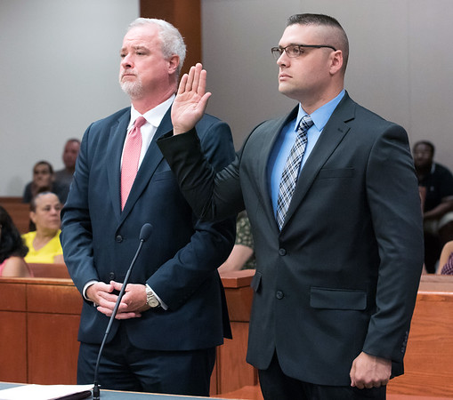 07/10/18 Wesley Bunnell | Staff Former New Britain and current Rocky Hill Police Officer Jacob Boucher raises his hand as he is sworn in at New Britain Superior Court on Tuesday morning. Boucher was arrested last week regarding a June 30 incident in New Britain.