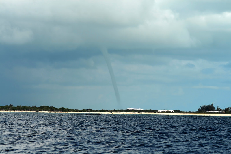Tornado touching down on land viewed from a body of water.