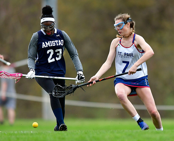 5/2/2019 Mike Orazzi | Staff Amistad's Randene Harris (23) and St. Paul's Reagan Davis (7) during Thursday's girls lacrosse in Bristol.