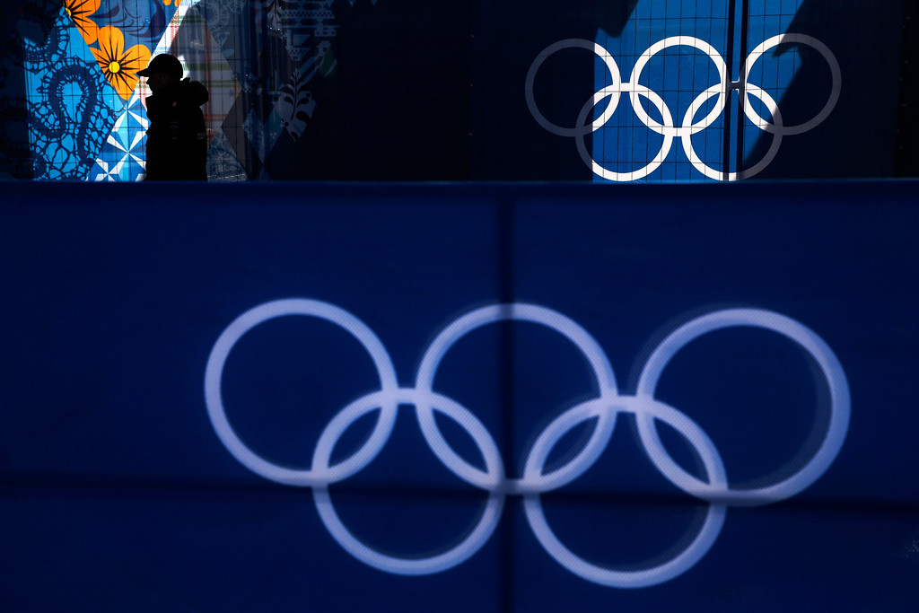 . A police officer walks along a fence past the Olympic rings in Krasnaya Polyana, Russia, during the 2014 Winter Olympics, Saturday, Feb. 22, 2014. (AP Photo/Jae C. Hong)