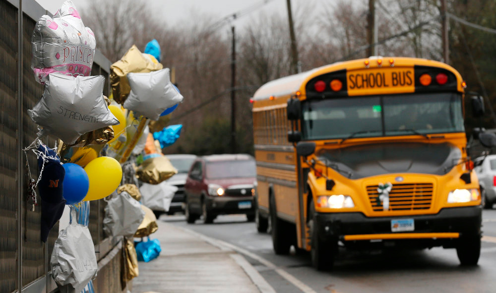 Description of . A school bus rolls towards a memorial for victims of the school shooting in Newtown, Conn., Tuesday, Dec. 18, 2012. Classes resume Tuesday for Newtown schools except those at Sandy Hook. Buses ferrying students to schools were festooned with large green and white ribbons on the front grills, the colors of Sandy Hook. At Newtown High School, students in sweatshirts and jackets, many wearing headphones, betrayed mixed emotions.  Adam Lanza walked into Sandy Hook Elementary School in Newtown,  Friday and opened fire, killing 26 people, including 20 children, before killing himself. (AP Photo/Charles Krupa)