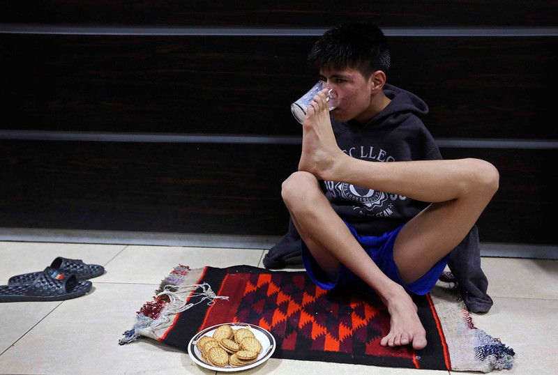 . Abbas Karimi, 14, who was born without arms, drinks milk using his foot to hold the cup in Kabul, February 12, 2013. Karimi has ambitions to earn a gold medal for his country in the world Paralympic games. If he gets the support he needs, the teenager will be the first Afghan to represent his county as a swimmer in the games next due to take place in Brazil in 2014. Picture taken on February 12, 2013. REUTERS/Omar Sobhani