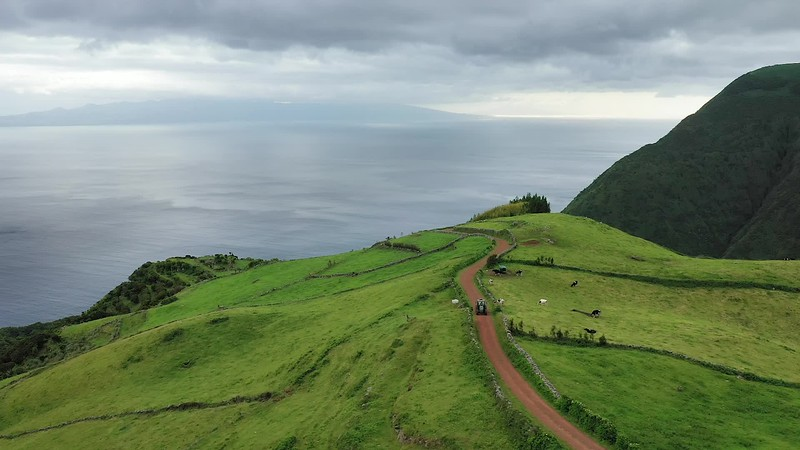 Available in 4K - Scenic hilly landscape panoram of the south coast of the island of Sao Jorge with a view on Pico island with the Ponta do Pico mountain in the clouds, Azores