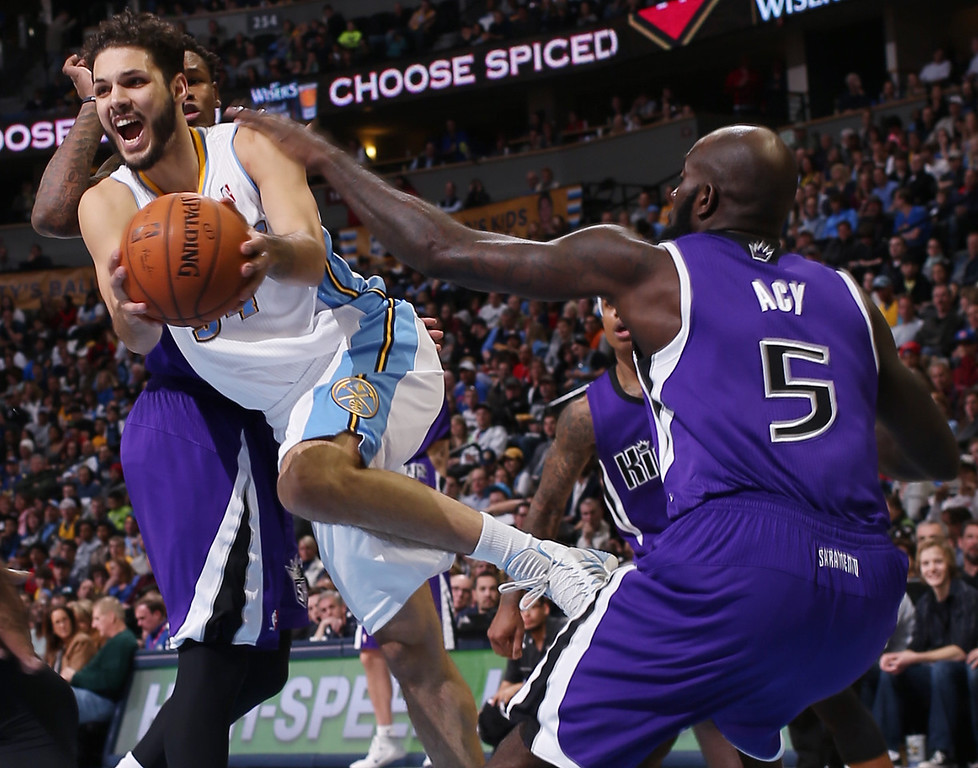 . Denver Nuggets guard Evan Fournier, of France, center, drives the lane for a shot as, from back left, Sacramento Kings forward Rudy Gay, guard Isaiah Thomas and forward Quincy Acy cover in the fourth quarter of an NBA basketball game in Denver, Sunday, Feb. 23, 2014. The Kings won 109-95. (AP Photo/David Zalubowski)