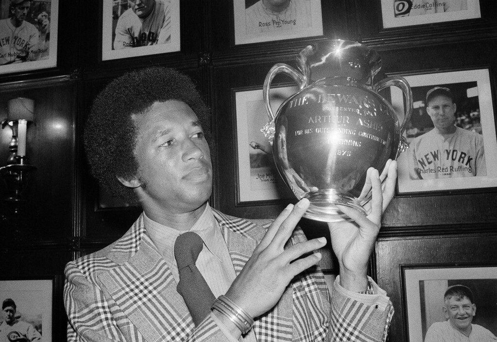 ". Wimbledon tennis champion Arthur Ashe of the U.S. admiringly looks over the Dewar Cup presented to him in New York for his ""outstanding contribution to tennis,\"" Aug. 26, 1975.   (AP Photo/Dave Pickoff)"