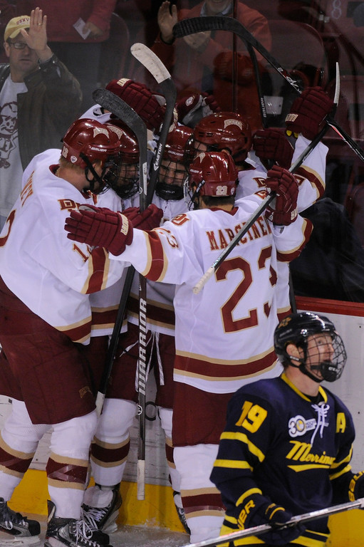 . DENVER, CO. - OCTOBER 12: Denver defenseman Joey LaLeggia (21) celebrated his first period power play goal with teammates Saturday night. The University of Denver hockey team hosted Merrimack at Magness Arena, Saturday night, October 12, 2013. Photo By Karl Gehring/The Denver Post
