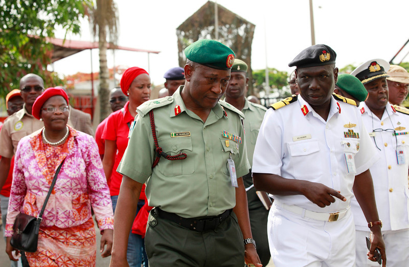 ". Brig. Gen. Chris Olukolade, Nigeria\'s top military spokesman, centre, walks with representatives of  kidnapped schoolgirls of Chibok secondary school, for a meeting at the defense  headquarters, in Abuja, Nigeria, Tuesday, May 6, 2014.  Their plight � and the failure of the Nigerian military to find them � has drawn international attention to an escalating Islamic extremist insurrection that has killed more than 1,500 so far this year. Boko Haram, the name means ""Western education is sinful,\"" has claimed responsibility for the mass kidnapping and threatened to sell the girls. The claim was made in a video seen Monday. The British and U.S. governments have expressed concern over the fate of the missing students, and protests have erupted in major Nigerian cities and in New York. (AP Photo/Sunday Alamba)"