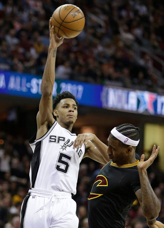 . San Antonio Spurs\' Dejounte Murray (5) passes over Cleveland Cavaliers\' Iman Shumpert (4) in the first half of an NBA basketball game, Saturday, Jan. 21, 2017, in Cleveland. (AP Photo/Tony Dejak)