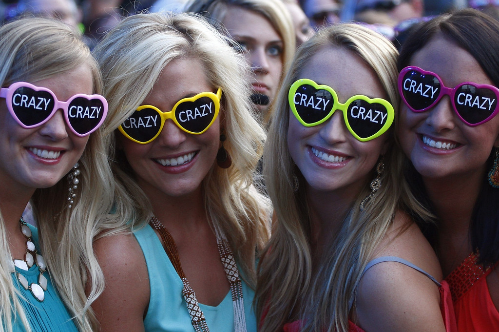 ". Fans wearing sunglasses promoting Hunter Hayes\' song ""Crazy\"" wait for him to perform at the 2013 CMT Music Awards at Bridgestone Arena on Wednesday, June 5, 2013, in Nashville, Tenn. (Photo by Wade Payne/Invision/AP)"