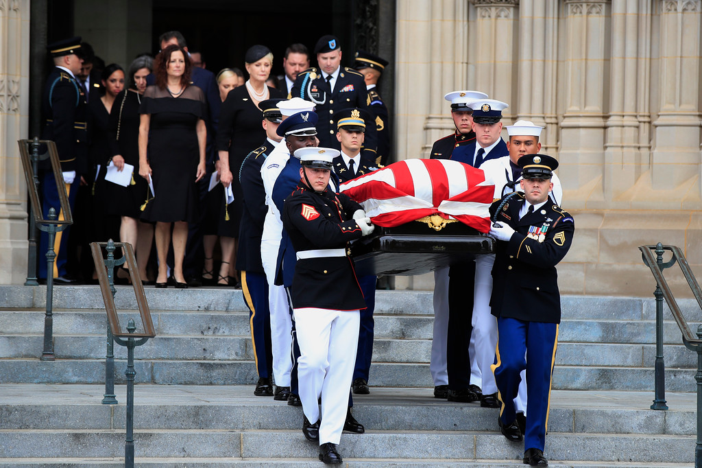 . Cindy McCain, center, widow of Sen. John McCain, R-Ariz., escorted by her son Jimmy McCain and other family members, follows his casket as it is carried out of Washington National Cathedral in Washington, Saturday, Sept. 1, 2018, following a memorial service. McCain died Aug. 25 from brain cancer at age 81. (AP Photo/Manuel Balce Ceneta)