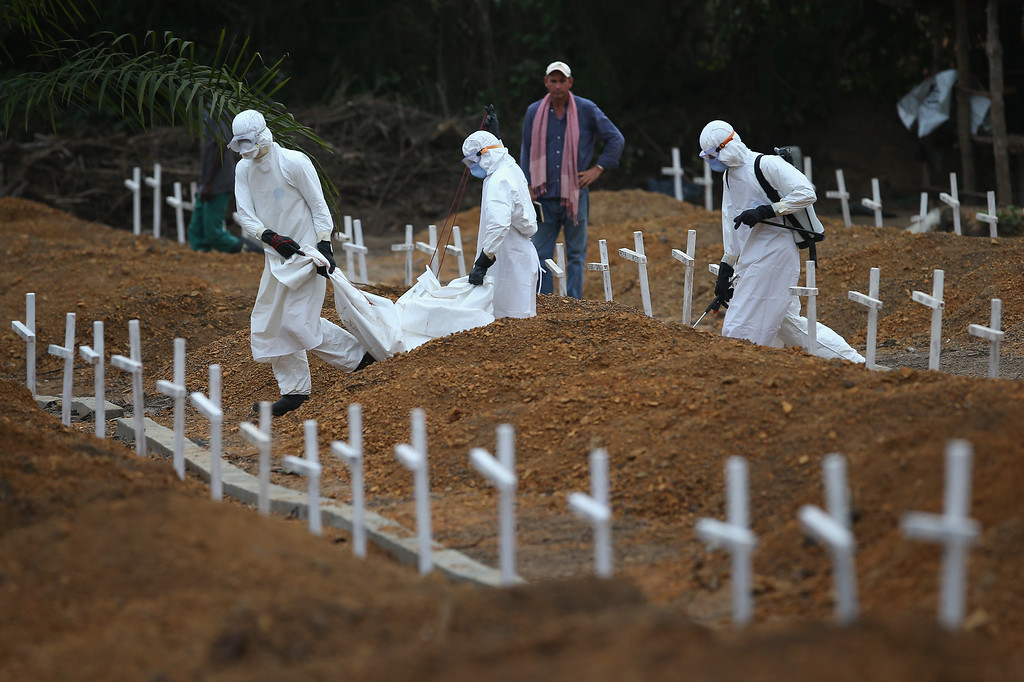 ". A burial team carries the body of a one-year-old to be interred at the U.S.-built cemetery for ""safe burials\"", as American Ebola response coordinator Matt Ward supervises on January 27, 2015 in Disco Hill, Liberia.  (Photo by John Moore/Getty Images)"