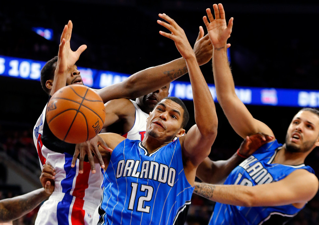 . Orlando Magic forward Tobias Harris (12) reaches for a rebound against Detroit Pistons center Andre Drummond (0) and  Anthony Tolliver (43) with Magic\'s Evan Fournier (10) in the second half of an NBA basketball game in Auburn Hills, Mich., Wednesday, Jan. 21, 2015. (AP Photo/Paul Sancya)