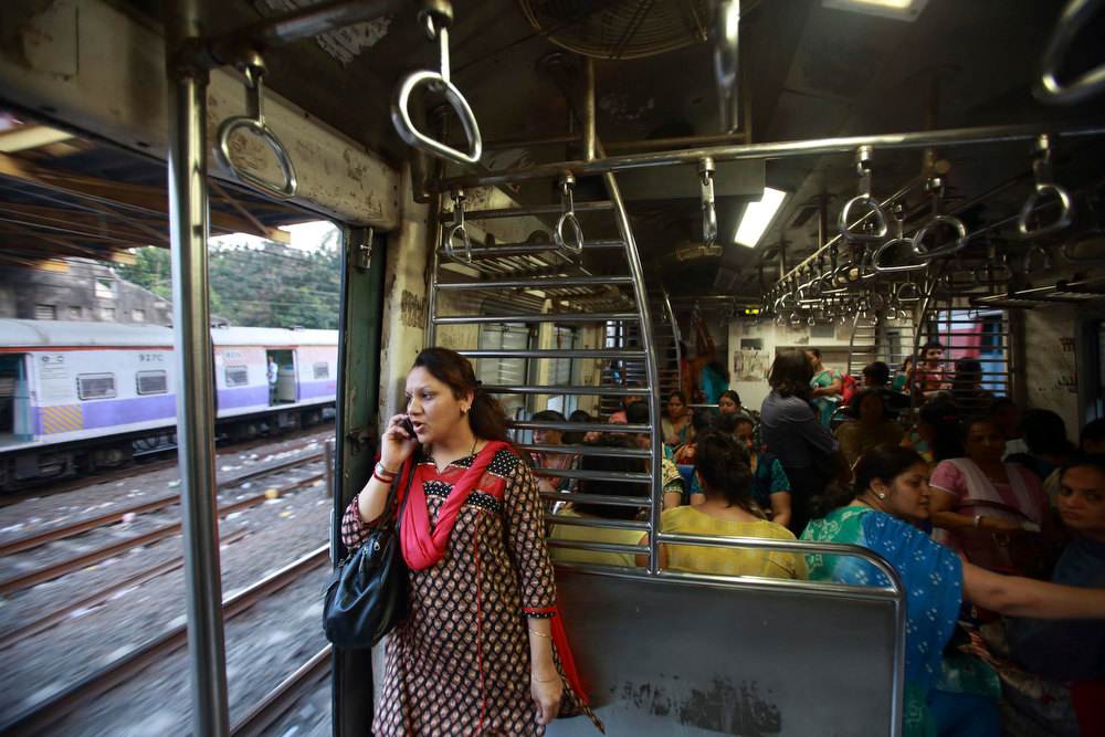 Description of . A woman speaks on the phone as she stands near the open doorway of a Ladies' Special train while travelling in Mumbai December 6, 2012.  In Mumbai there are two trains every day except Sunday reserved especially for women. In India some train compartments, or sometimes whole trains, are reserved specifically for female passengers in an effort to make their travel easier and more secure. The role and treatment of women in society has recently become a hot political issue in the country, since the Dec. 16 gang rape of a 23-year-old student in New Delhi, who later died of her injuries, and whose case has led to widespread protests in the region against violence against women. Picture taken December 6, 2012. REUTERS/Navesh Chitrakar