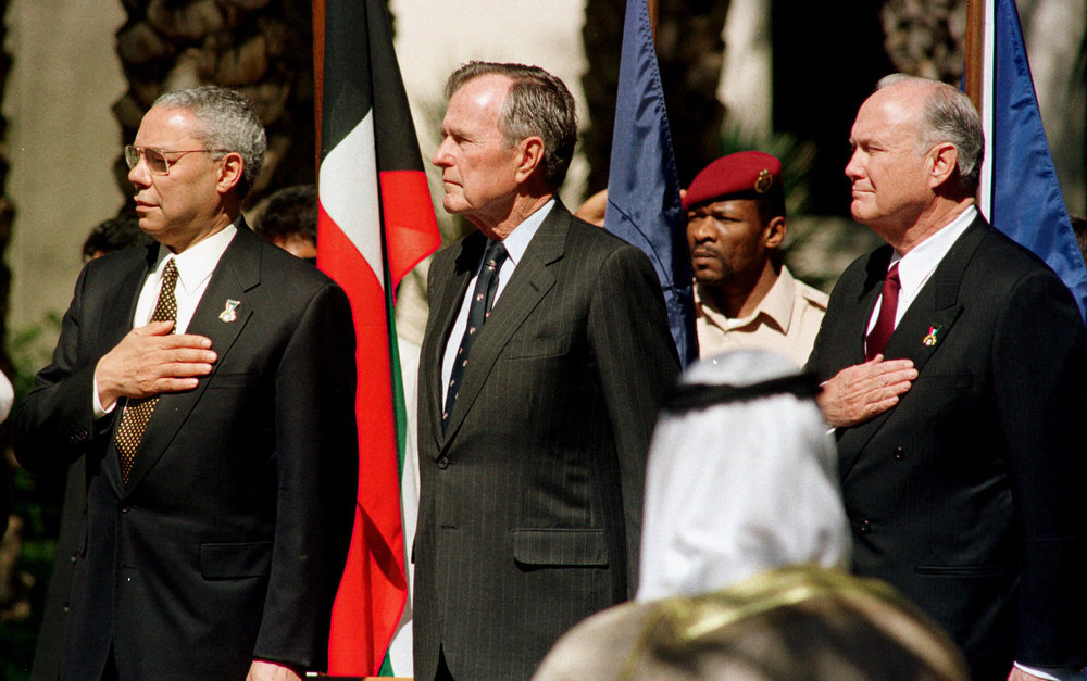 . Former U.S. President George Bush, center, U.S. Secretary of State Colin Powell, left, and retired General Norman Schwarzkopf, right, stand at attention during the playing of the National Anthem Monday, Feb. 26, 2001, at the American Embassy in Kuwait at the ceremony marking the 10th anniversary of the liberation of Kuwait. (AP Photo/Gustavo Ferrari)