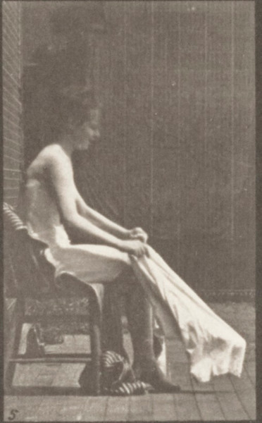 Nude woman rising from a chair and putting on clothing