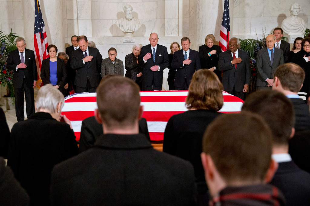 . Supreme Court Justices make the sign of the cross during prayers at a private ceremony in the Great Hall of the Supreme Court in Washington, Friday, Feb. 19, 2016, where late Supreme Court Justice Antonin Scalia lies in repose. In back, from left are, Counselor to the Chief Justice Jeffrey Minear, and Supreme Court Justices Elena Kagan, Samuel Anthony Alito, Jr., Ruth Bader Ginsburg, Anthony Kennedy, Chief Justice John Roberts, Jr., Clarence Thomas, Stephen Breyer, and Sonia Sotomayor. (AP Photo/Jacquelyn Martin, Pool)