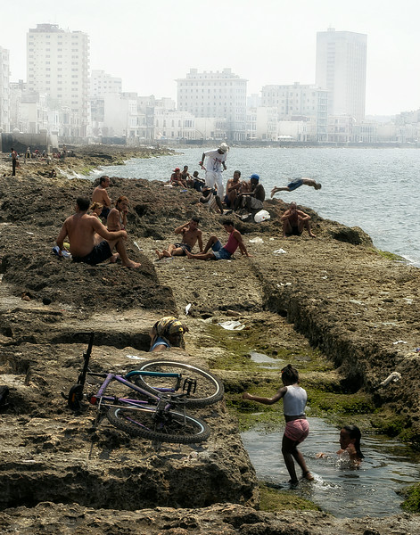Great efforts have been made in recent years to clean up the waters off the Malecon in the bay of Havana. Although not yet perfectly clean, locals sometimes have no choice but to cool down here in order to escape the intense heat.   Havana, Cuba, 2006.