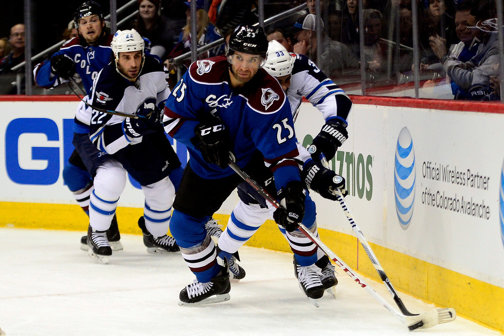 . Maxime Talbot (25) of the Colorado Avalanche controls the puck as Dustin Byfuglien (33) of the Winnipeg Jets defends during the first period of action.  (Photo by AAron Ontiveroz/The Denver Post)
