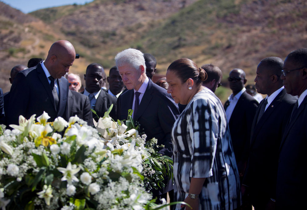 Description of . Haiti\'s President Michel Martelly, left, UN special envoy to Haiti and former President Bill Clinton, center ,and Haiti\'s first lady Sophia Martelly, right center, attend a memorial service for victims of the 2010 earthquake, at Titanyen, a mass burial site north of Port-au-Prince, Haiti, Saturday, Jan. 12, 2013. Haitians recalled the tens of thousands of people who lost their lives in a devastating earthquake three years ago, marking the disaster\'s anniversary Saturday with a simple ceremony. Haiti\'s previous presidential administration said 316,000 people were killed but no one really knows how many died.  (AP Photo/Dieu Nalio Chery)