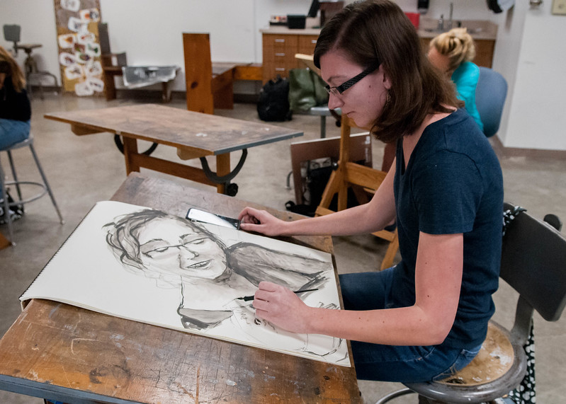 Student Courtni Whetsell working on a pen and ink self portrait.