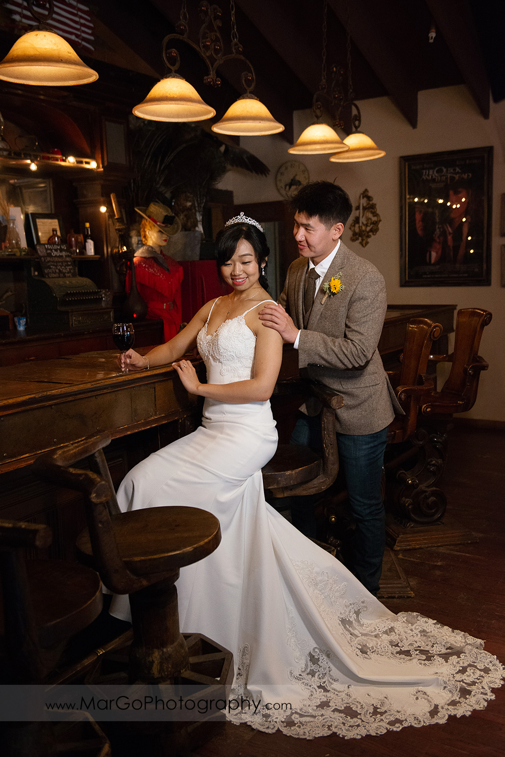full body portrait of sitting bride and standing groom in the saloon at Long Branch Saloon & Farms in Half Moon Bay