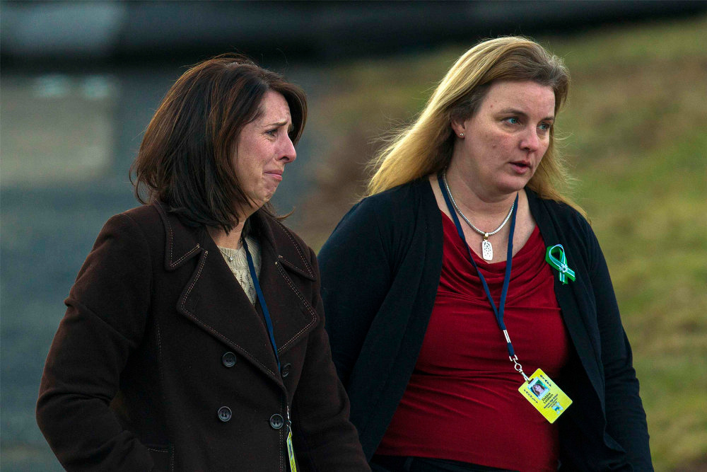 Description of . Faculty members of Newtown High School react emotionally as they leave a viewing honoring school principal Dawn Hochsprung, a victim in the Sandy Hook Elementary School shooting, in Woodbury, Connecticut, December 19, 2012. Six victims of the Newtown school shooting will be honored at funerals and remembrances on Wednesday, including the school principal who was killed with 20 of her students and five other staff members at the Sandy Hook Elementary School. REUTERS/Lucas Jackson