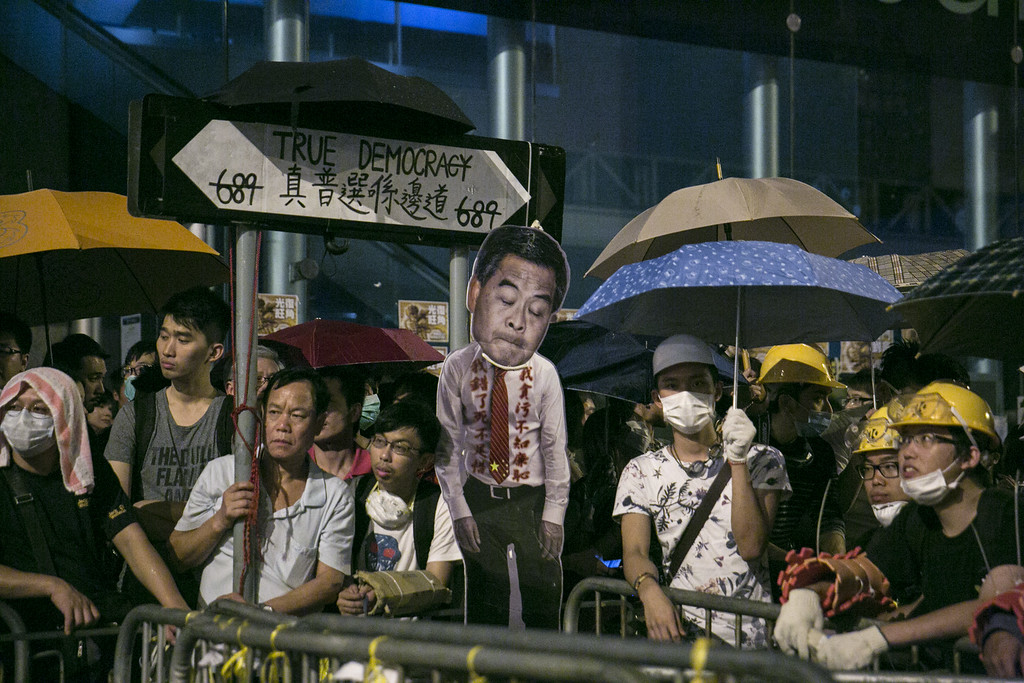 . HONG KONG - OCTOBER 18:  Pro-democracy protesters stand next to a barricade after reclaiming streets in Mong Kok after scuffles with police October 18, 2014 in Hong Kong, Hong Kong. Police have begun to take measures to remove the blockades put in place by pro democracy supporters following weeks of protests. Hong Kong\'s Chief Executive Leung Chun-ying today called for talks to resume between protest groups and government officials and said his government is ready to meet with student leaders to discuss \'universal suffrage.  (Photo by Paula Bronstein/Getty Images)