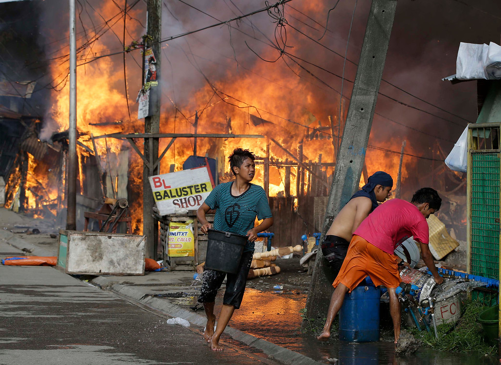 . Residents try to put out a fire that gutted several homes while government troopers continue their assault on Muslim rebels Thursday, Sept. 12, 2013, in Zamboanga city in the southern Philippines. (AP Photo/Bullit Marquez)