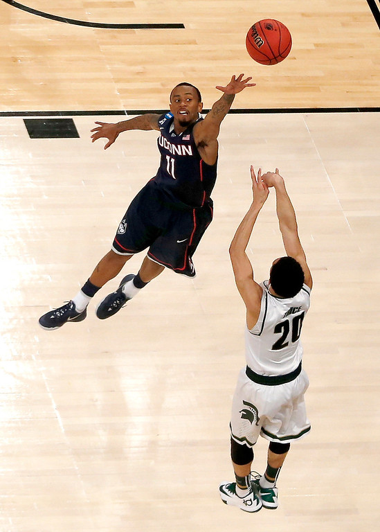 . Michigan State guard Travis Trice (20) shoots against Connecticut guard Ryan Boatright (11) during the first half in a regional semifinal at the NCAA college basketball tournament, Sunday, March 30, 2014, in New York. (AP Photo/Julio Cortez)