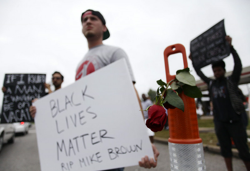 . A rose hangs from a construction cone during a protest of Michael Brown\'s murder August 17, 2014 in Ferguson, Missouri.Tensions still run high in the Ferguson community after 18 -year-old Michael Brown was killed by a Ferguson Police Officer August 9 on Canfield Drive. (Photo by Joshua Lott/Getty Images)