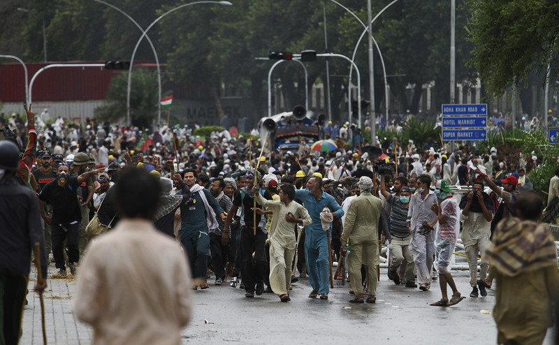 . Pakistani protesters run to chase police officers during clashes in Islamabad, Pakistan on Monday, Sept. 1, 2014. Anti-government protesters and Pakistani police have clashed once again as the demonstrators pushed into a sprawling government complex in the country\'s capital in an effort to try to reach the prime minister\'s official residence. (AP Photo/Anjum Naveed)