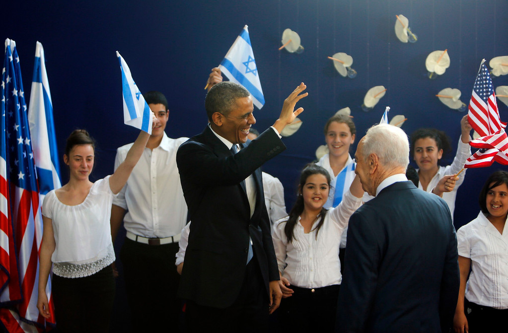 . U.S. President Barack Obama waves as he stands with Israel\'s President Shimon Peres (back to camera) during a welcoming ceremony at Peres\' residence in Jerusalem March 20, 2013.  REUTERS/Ronen Zvulun