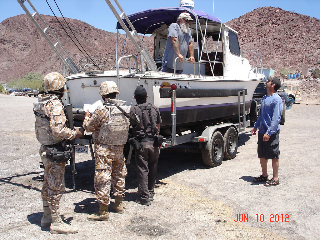 . Mexican marine and navy officials inspect Joe Jacinto, right, and his team\'s boat, including Wings Stocks (on board) on the beach of Gonzaga Bay in June 2012.  (Courtesy of Joe Jacinto)