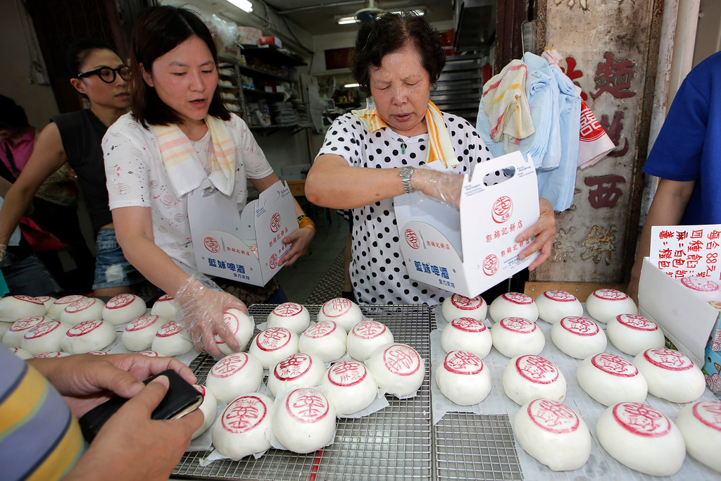 """. Shopkeepers sell the buns with the sign featuring the Chinese character \""""Peace\"""" on the outlying Cheung Chau island in Hong Kong to celebrate the Bun Festival Tuesday, May 22, 2018. Thousands of local residents and tourists flocked to an outlying island in Hong Kong to celebrate a local bun festival on Tuesday despite the recording-breaking heat.  The festival features a parade with children dressed as deities floated on poles. Later on Tuesday, contestants will take part in bun-scrambling competition. They will race up a 14-meter bamboo tower to snatch as many plastics buns as possible. Buns that are higher up are worth more points.  (AP Photo/Kin Cheung)"""