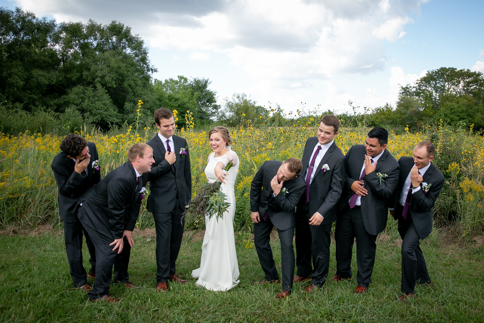 seven groomsmen jokingly looking at the bride's engagement ring in awe