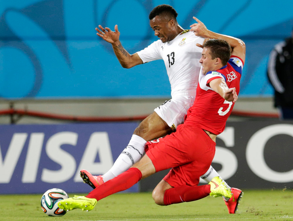 Description of . United States' Matt Besler, right, slides under Ghana's Jordan Ayew to take the ball away during the group G World Cup soccer match between Ghana and the United States at the Arena das Dunas in Natal, Brazil, Monday, June 16, 2014.  (AP Photo/Petr David Josek)