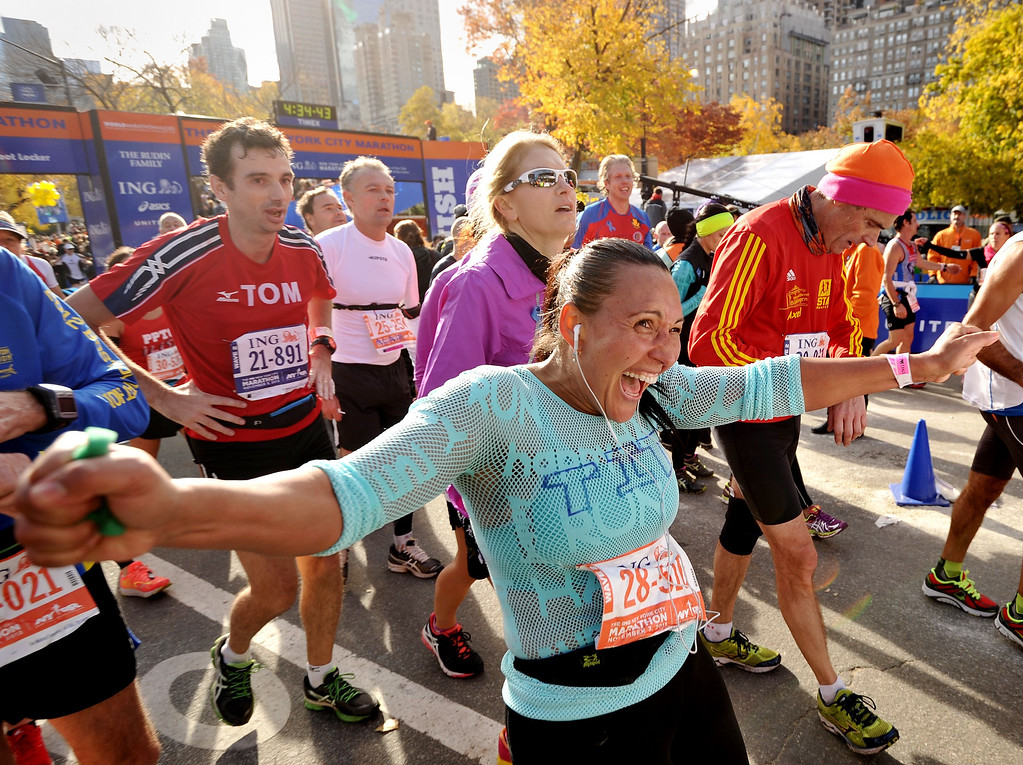. A woman and other runners cross the finish line at the New York City Marathon on November 3, 2013 in New York.   STAN HONDA/AFP/Getty Images