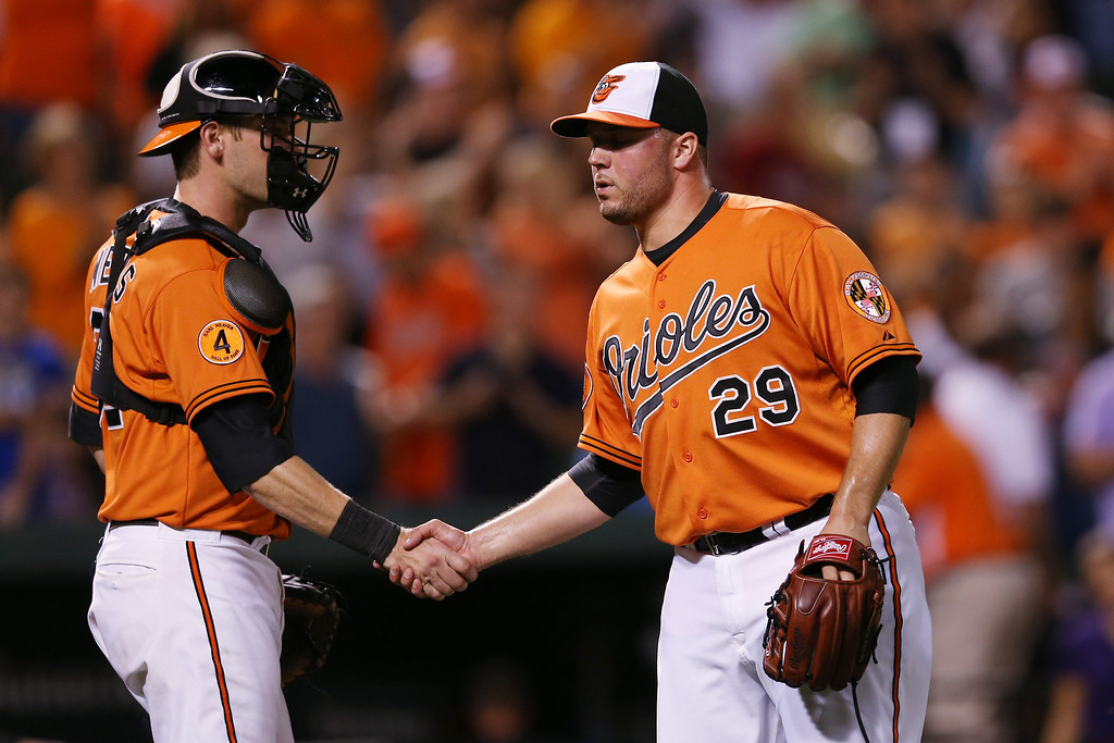 . BALTIMORE, MD - AUGUST 17: Catcher Matt Wieters #32 and pitcher Tommy Hunter #29 of the Baltimore Orioles celebrate following the Orioles 8-4 win over the Colorado Rockies at Oriole Park at Camden Yards on August 17, 2013 in Baltimore, Maryland.  (Photo by Rob Carr/Getty Images)