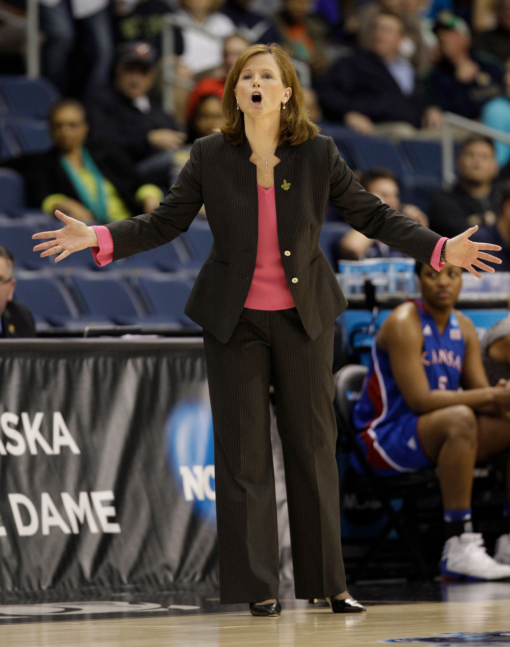 Description of . Kansas head coach Bonnie Henrickson directs her team during the first half of a regional semi-final of the NCAA college basketball tournament Sunday, March 31, 2013, in Norfolk, Va.  (AP Photo/Steve Helber)