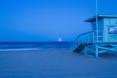 The moon sets over the ocean at sunrise in Hermosa Beach, CA.