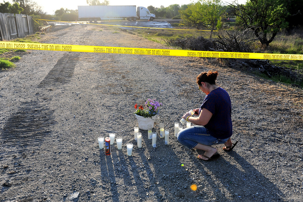 . Ana Garcia lights candles near the scene of the collision between the FedEx truck and the bus carrying high school students on the I-5, Friday, April 11, 2014, in Orland, Ca. (Photo by Michael Owen Baker/L.A. Daily News)