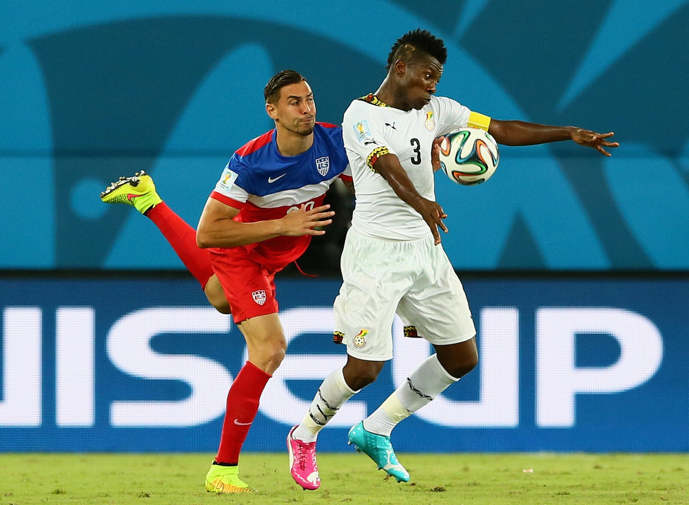 Description of . NATAL, BRAZIL - JUNE 16: Asamoah Gyan of Ghana competes for the ball with Geoff Cameron of the United States during the 2014 FIFA World Cup Brazil Group G match between Ghana and the United States at Estadio das Dunas on June 16, 2014 in Natal, Brazil.  (Photo by Kevin C. Cox/Getty Images)