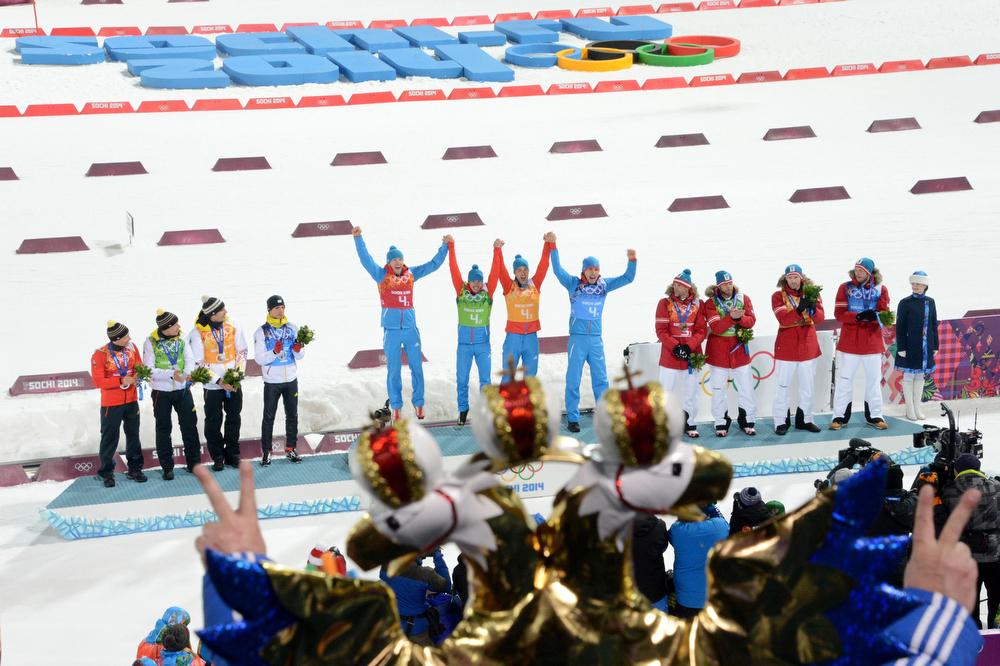 . (LtoR) Silver medalists Germany\'s Erik Lesser, Daniel Boehm, Arnd Peiffer, Simon Schempp, gold medalists Russia\'s Anton Shipulin, Dmitry Malyshko, Evgeny Ustyugov, Alexey Volkov and bronze medalists Austria\'s Christoph Sumann, Daniel Mesotitsch, Simon Eder and Dominik Landertinger celebrate at the podium in the Men\'s Biathlon 4x7.5 km Relay Medal Ceremony at the Laura Cross-Country and Biathlon Center during the Sochi Winter Olympics on February 22, 2014, in Rosa Khutor, in Sochi.  (KIRILL KUDRYAVTSEV/AFP/Getty Images)