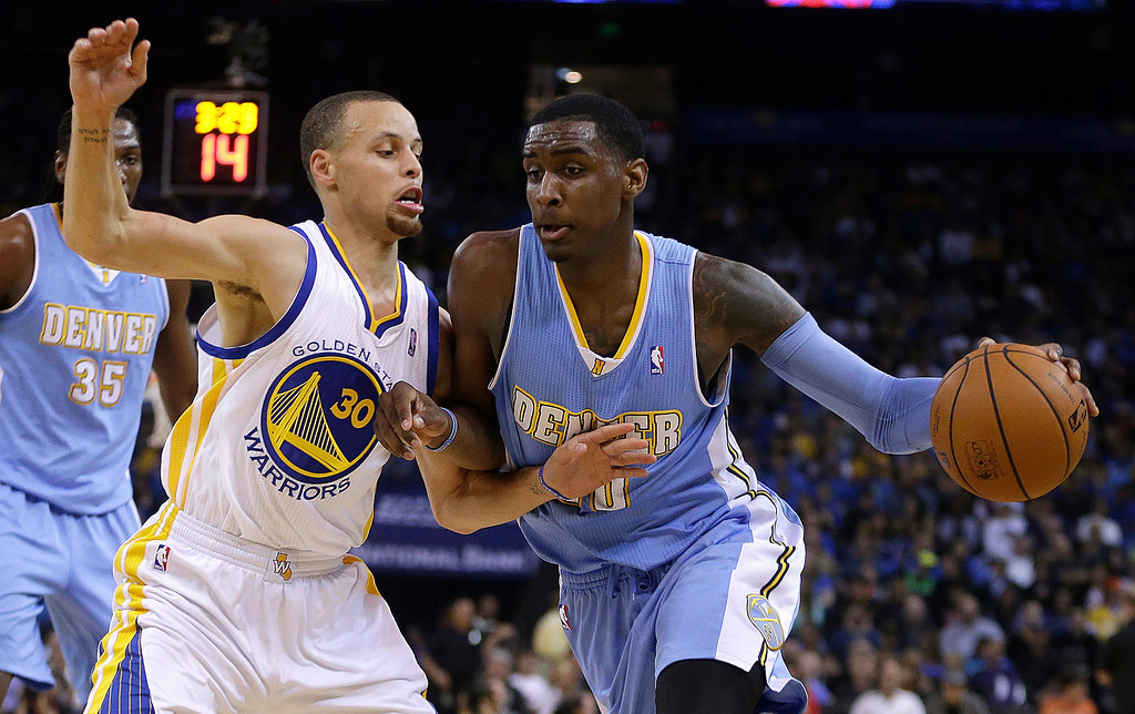 . Denver Nuggets\' Quincy Miller, right, drives the ball against Golden State Warriors\' Stephen Curry (30) during the first half of an NBA basketball game Thursday, April 10, 2014, in Oakland, Calif. (AP Photo/Ben Margot)