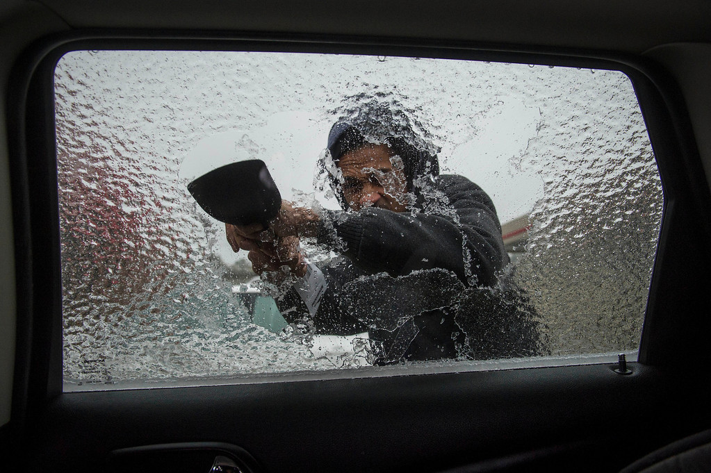 . Lamarr Lewis scrapes ice from his car window during a winter storm on Wednesday, Feb. 12, 2014, in Doraville, Ga. (AP Photo/John Amis)