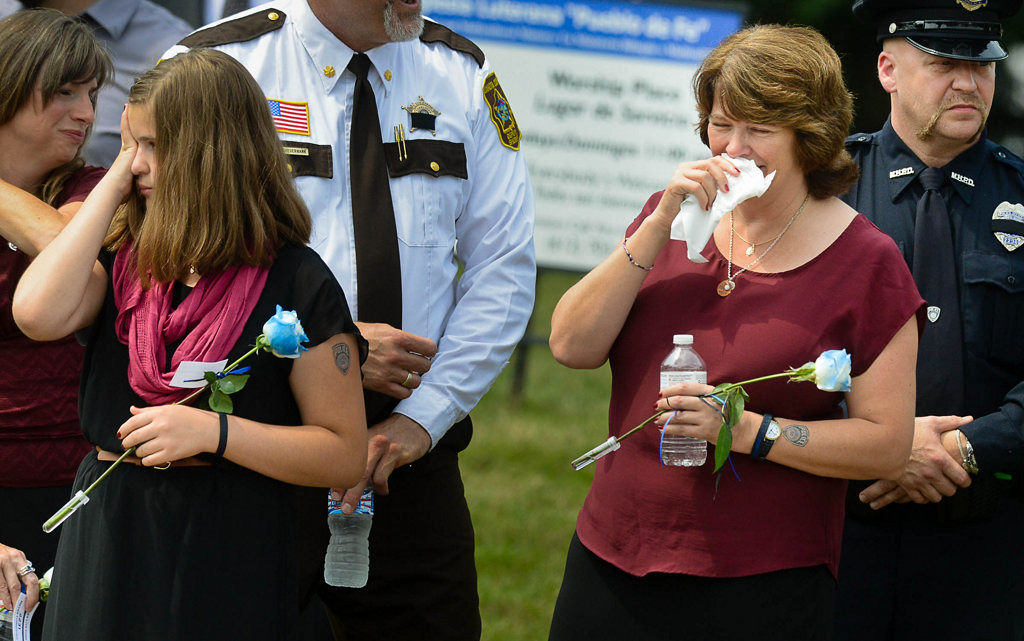 . Michelle Patrick, right, widow of Mendota Heights officer Scott Patrick, and daughter Amy, 13, left, watch as hundreds of police cars pass by in  procession to the cemetery after the funeral service at St. Stephen\'s.  (Pioneer Press: Ben Garvin)